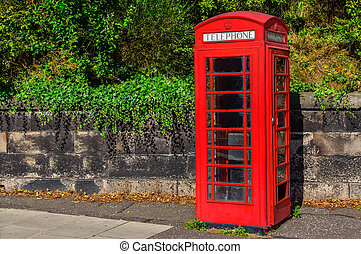 Typical red English telephone booth in the park - Typical...