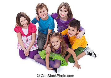 Group of kids sitting on the floor holding to each other -...