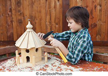 Boy building a bird house - mounting the last roof piece...