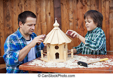Father and son working on bird house together polishing it...
