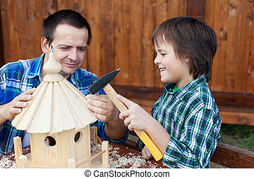 Father and son building a bird house or feeder for the...