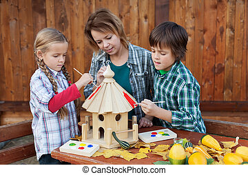 Woman with kids painting the bird house - preparing for winter