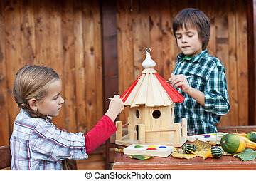 Kids painting the bird house for the winter - care for...