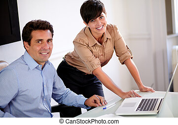 Attractive professional couple smiling at you - Portrait of...