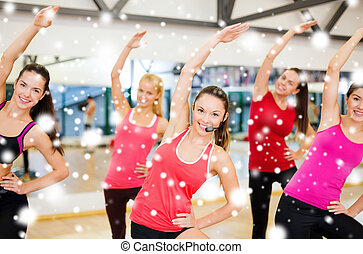 group of smiling people stretching in the gym - fitness,...