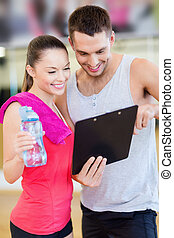 smiling male trainer with woman in the gym - fitness, sport,...