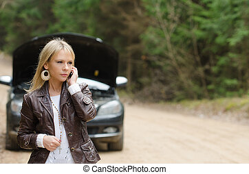 woman at broken car with phone - Young woman at broken car...
