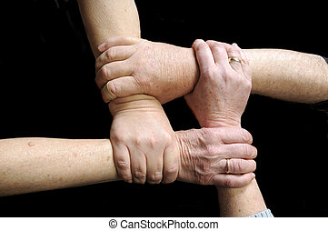 Hands joined in union - 4 older freinds joining Hands in...