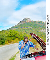 Adult man is calling to support standing beside broken car