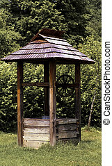 Old wooden well with metal bucket and green background, size...