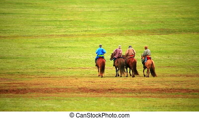 People riding horses in Mongolian landscape