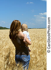 mother with child at the wheat field - mother holding a...