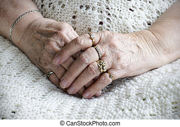 Senior woman hands crossed on her legs: loneliness or health...