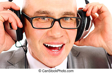 Close-up of a smiling businessman wearing headphones looking...