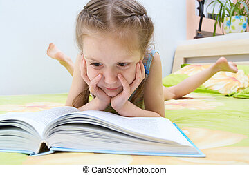 child reading a book - little child girl laying on a bed and...