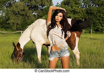 Attractive brunette beauty posing - Sexy cowgirl posing at...