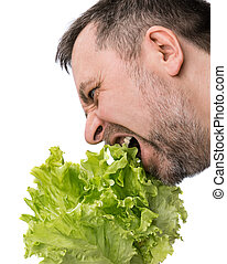 Organic food. Man eating salad lettuce isolated on white