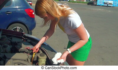 Blonde opens the hood of a car