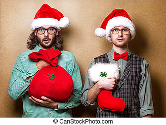 Two hipster in Santa Claus clothes with the bag of the...