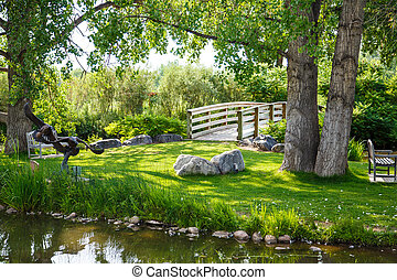 Benches in Grass Between Bridge and Pond - A peaceful green...