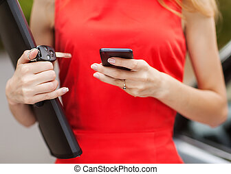 Young beautiful woman writes an SMS to your mobile phone.