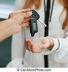 Male hand giving car key to female hand. She is holding a...