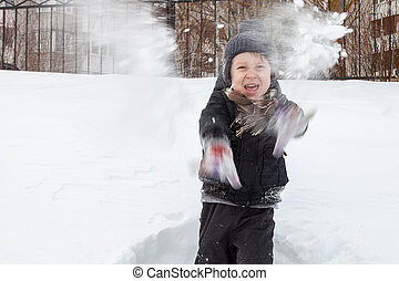 Boy plays in the snow - Young boy in knitted hat throws...