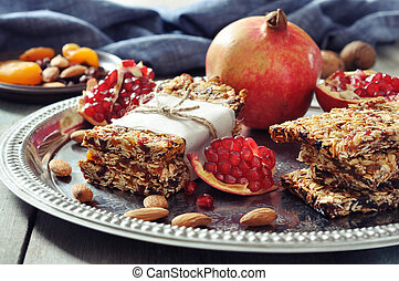 Granola bars on plate with nuts, pomegranate and dried...
