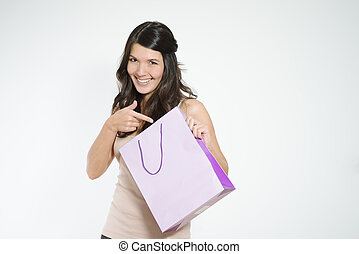 Happy shopper pointing to her shopping bag with a playful...