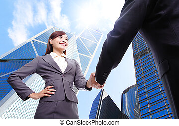 Business woman and man handshake with business office...