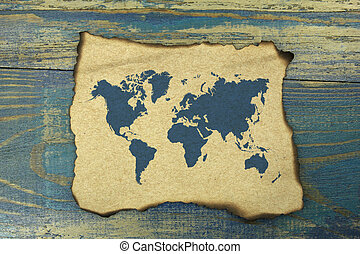 world map on burnt paper on blue old wood background