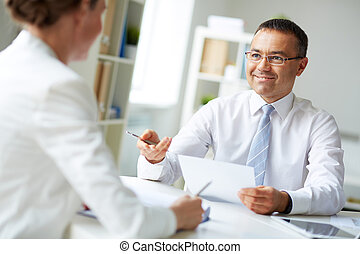 Speaking at meeting - Mature businessman looking at his...