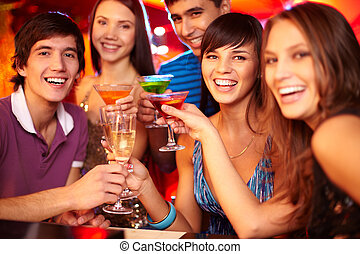 Cheering friends - Portrait of joyful friends toasting and...