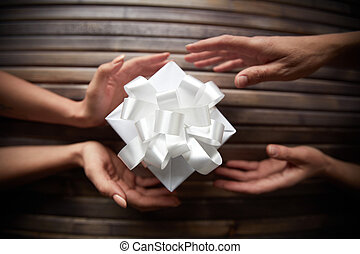 Giving Christmas present - Image of female hands giving...