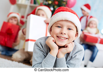 Little Santa - Image of cute lad in Santa cap looking at...