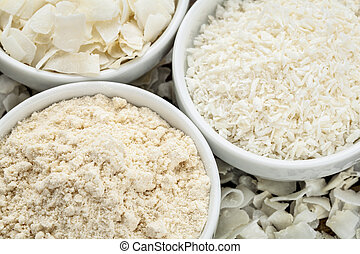 coconut flour and flakes in three white ceramic bowls