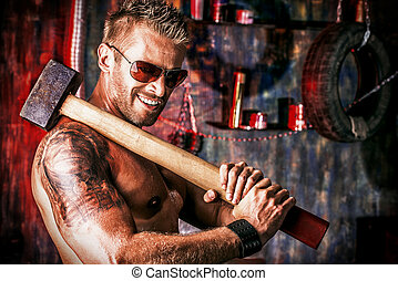 unshaven - Handsome muscular man with sledgehammer working...