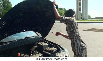 Brunette opens the hood of a car