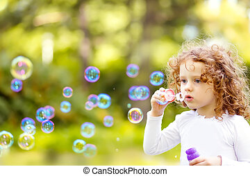 A little girl blowing soap bubbles, closeup portrait...