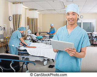 Nurse With Digital Tablet Standing In Post Surgery -...