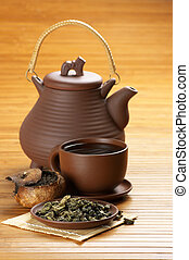 Tea set - Dried tea, cup of tea and teapot on wooden...