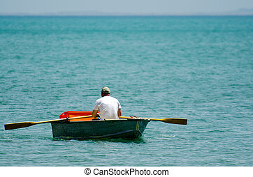 Man row dinghy - Man row a small wooden rowboat dinghy over...