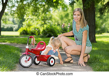 Mother With Daughter Crouching By Tricycle On Walkway -...