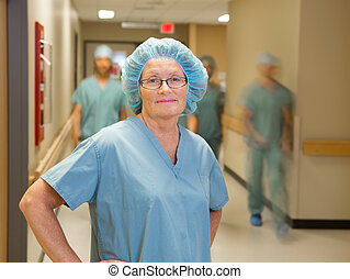 Doctor With Team Walking In Hospital Corridor - Portrait of...