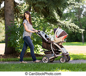 Beautiful Mother Pushing Baby Carriage In Park - Full length...