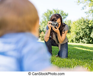 Woman Photographing Baby Son - Happy young woman...