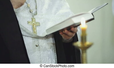 Church service - Priest prays with the Bible in the hands...
