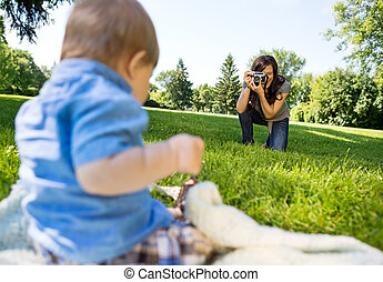 Woman Photographing Baby Boy In Park - Happy young woman...
