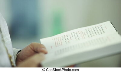 Bible - Priest holding an open Bible and praying