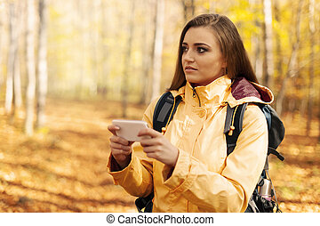 Confused young hiker with smart phone in forest